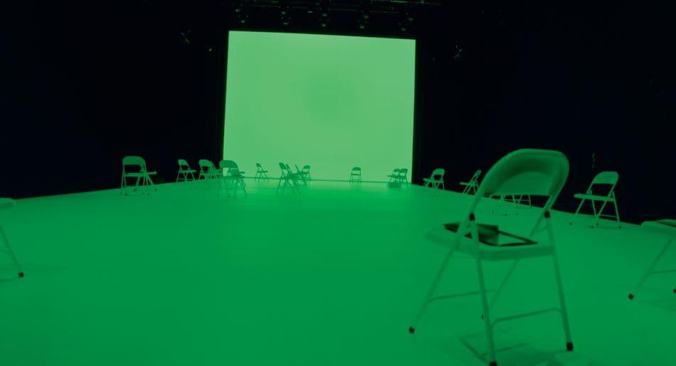 Bottega Veneta Salon 01 London, il lancio della collezione Spring 2021. In una location misteriosa avvolta da una luce verde, ci sono delle sedie vuote che attendono i pochi invitati. Fonte: Icon
